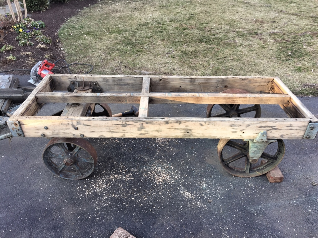 Cart after rotted wood was removed, frame shortened, power-washed and sanded. I love the hand-hewn cross beam in the middle.